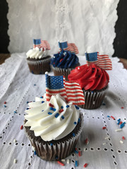 Patriotic cupcakes with american flags on white linen
