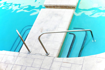 Staircase into swimming pool with railing on both sides, seen from above