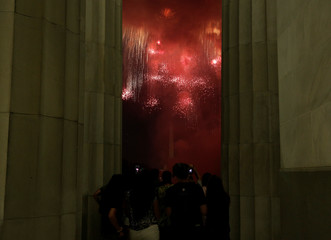 People watch fire works explode at the Lincoln Memorial in celebration of 241st anniversary of the Declaration of Independence in Washington