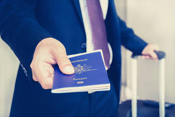 Businessman giving passport with boarding  pass inside