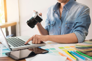 Photography Ideas Creative Occupation Design Studio Concept, Female photographer sitting on the desk with laptop