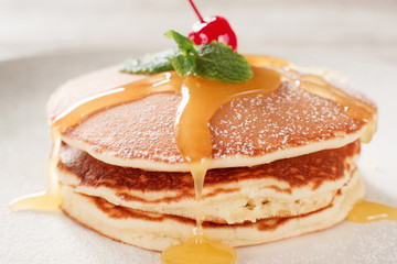 American pancakes with honey topping. Cooking food. Crepe with cherry on white plate background. Traditional US meal.
