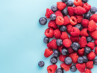 Raspberry and blueberry on blue background with copy space