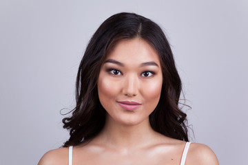 Portrait of a beautiful asian woman with makeup and light curls.