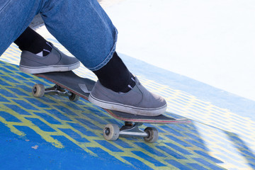 Closeup of teenager having break in a skate park on summer day outdoors side view Skater with skateboard sitting and chilling at urban area
