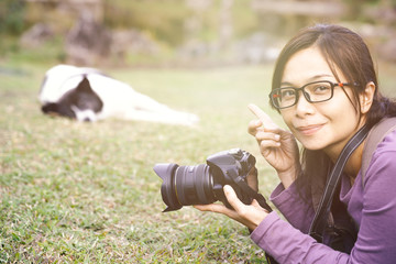 Asian woman holding camera and pointing to the dog.