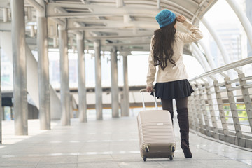 Asian woman holding luggage for travel