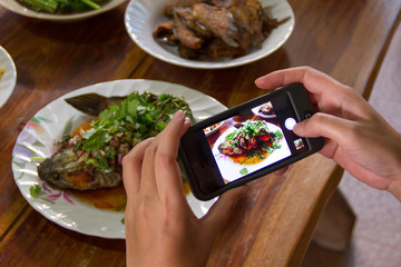Women using mobile phones to take pictures of food