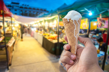 Man hold a cone ice cream and blurred image of street market at night.
