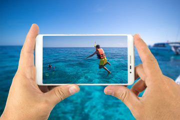 Hand holding a smart phone taking photograph boys jumping into the sea.