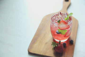 Strawberry juice cocktail with ice and mint on white tone amd wooden