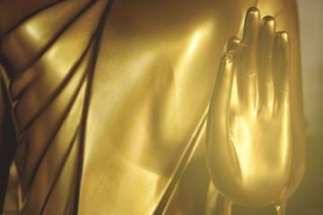Close up Hand of Golden Buddha Image with Light Leak.