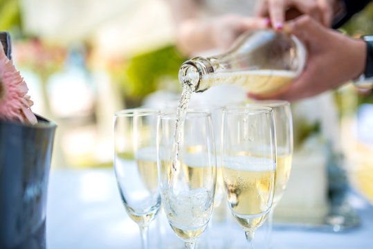 Bride and groom pour into a glass of champagne at a wedding ceremony.