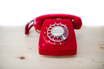 Dirty red vintage phone on pine wooden table.