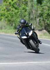 The biker on the black sports motorcycle on a bend on speed