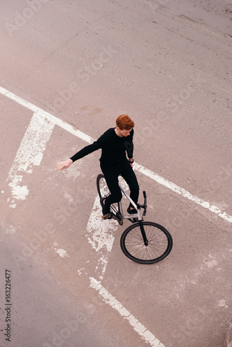 Young handsome redhead man riding a bicycle on the road  Stylish fix