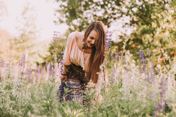 Young beautiful brown hair hippie girl gathering flowers and walking through meadow in sunny day. Summer field. Great force of unity with the Nature. Outdoors