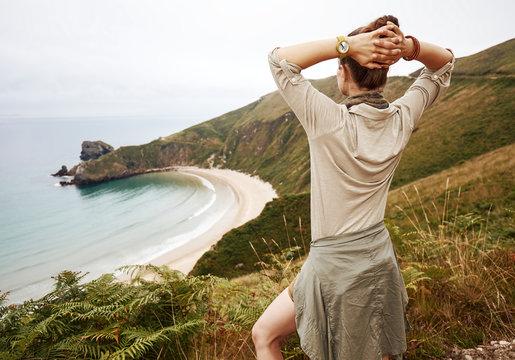 Seen from behind woman hiker enjoing ocean view landscape