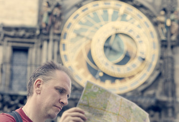 man examines the map on background of historical medieval astronomical Clock on the Old Town Hall in Prague, Czech Republic, retro effect..