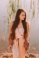 Young beautiful brunette woman in bo ho clothes walks on the lake shore near forest. River at warm summer sunny day. Outdoor. Sunset
