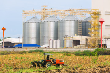 Agricultural Silos - Building Exterior, Storage and drying of grains, wheat, corn, soy, sunflower against the blue sky with farm tractors in the foreground.