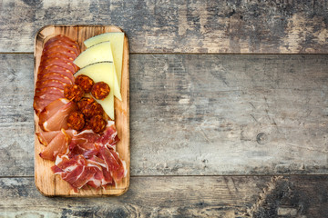 Spanish cold cuts (embutidos). Cheese, sausage and ham on wooden table