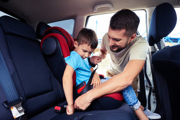 Concentrated father helps his son to fasten belt on car seat