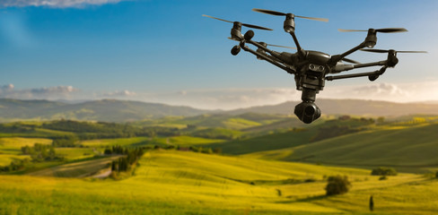 A flying drone with camera with blured hills of Tuscany in the background