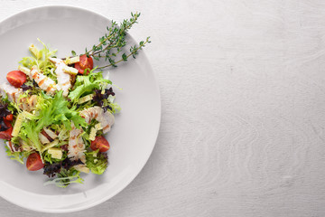 Fresh vegetables and grilled chicken salad. On a wooden background. Top review. Free space.