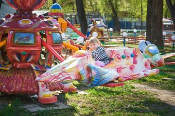 Маленькая девочка катается на каруселях в летнем парке аттракционов