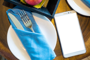 Top view of smartphone in empty placed on a luxury dinner table.