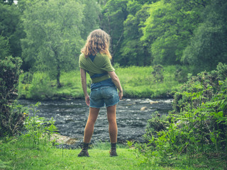 Young woman standing by river in nature