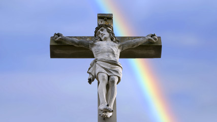 stone cross with Jesus and blue sky with rainbow