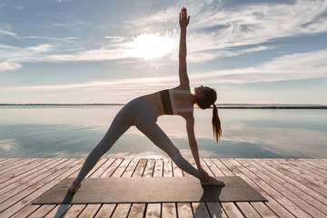 In de dag School de yoga Sports lady standing at the beach make yoga exercises.