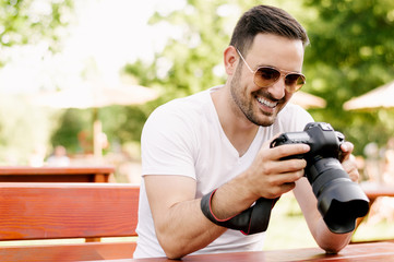 Man looking at photos he taken on dslr