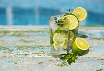 Glasses of homemade lemonade on a rustic wooden background