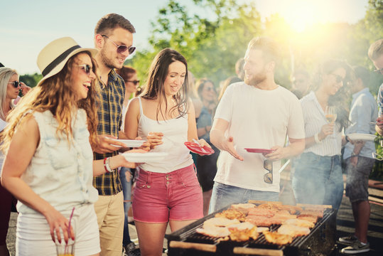 Friends having outdoor party and eating barbecue