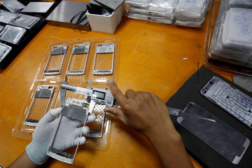 A worker measures a metal frame at an assembly plant that produces the Vietnamese smartphone BPhone, at BKAV factory, in Hanoi