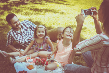 Happy family enjoying in picnic together. Family in meadow. Mother making self-picture.