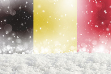 Defocused Belgium flag as a winter Christmas background with falling snow, snowdrift and bokeh