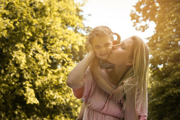 Mother and daughter outdoors in a meadow.  Mother and daughter playing on green grass. Mother kissing her daughter.