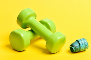 Pair of shiny green plastic dumbbells and rolled measuring tape
