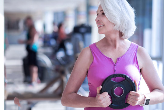 Aged woman holding barbell at gym