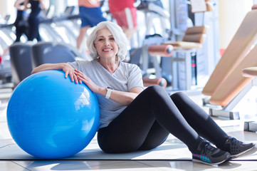 Senior woman lying near fitness ball