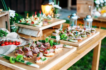 Deurstickers Buffet, Bar Beautiful catering banquet buffet table decorated in rustic style in the garden. Different snacks, sandwiches. Outdoor.