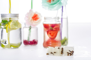 jars of water with fruits and berries decorated with flowers, selective focus on ice cubes at foreground