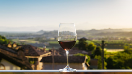 Single wine glass above vineyards, Piedmont, Italy