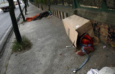 People sleep on the sidewalk, one of them inside a box, in Buenos Aires