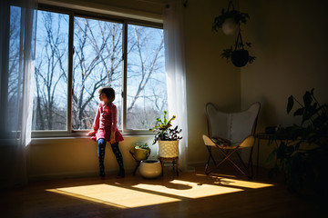 Girl sitting in sunlight looking through a window