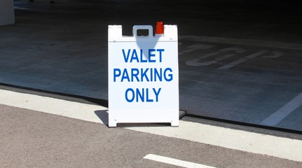A valet parking only sign in front of the entrance to the parking garage.